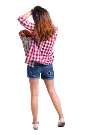 Back view of woman with  basket of dirty laundry. girl is engaged in washing. Rear view people collection.  backside view of person.  Isolated over white background. Girl in shorts holding a laundry basket and the second arm straightens hair. Stock Photo