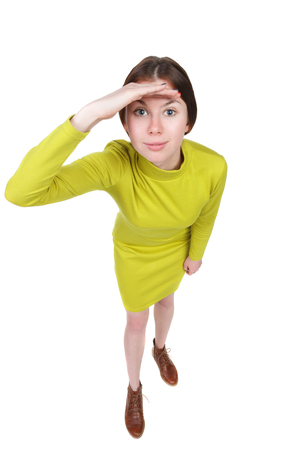 Funny portrait of a woman gazing into the frame. Wide-angle. Isolated over white background. A girl in a short purple dress looks in the frame. Stock Photo