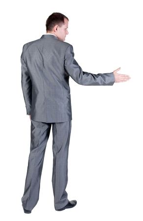 extending: businessman extending hand to shake. Rear view. Isolated over white background. Stock Photo