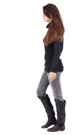 back view of walking  woman  in  gray jeans. beautiful brunette girl in motion.  backside view of person.  Rear view people collection. Isolated over white background. Stock Photo