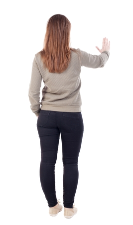 back view of woman. Young woman presses down on something. Isolated over white background. Rear view people collection. backside view of person. she holds his hand open, palm forward. The girl in a jacket with a fur top is...