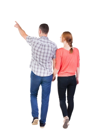 treading: Back view of walking young couple (man and woman) pointing. Rear view people collection. backside view of person. Isolated over white background Stock Photo