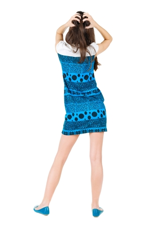 back view of shocked beautiful  young woman . Girl in blue dress. Rear view. Isolated over white
