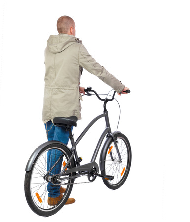 back view of a man with a bicycle. Cyclist in parka jacket keeps the wheel of a bicycle. Rear view people collection.  backside view of person. Isolated over white background. photo