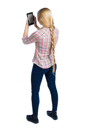 back view of standing young beautiful  girl with tablet computer in the hands of. girl  watching. Rear view people collection.  backside view of person.  Isolated over white background. Long-haired blonde in a checkered shirt looking into e-book reader. Stock Photo