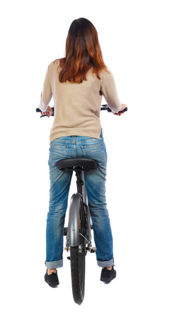 back view of a woman with a bicycle. cyclist sits on the bike. Rear view people collection.  backside view of person. Isolated over white background. Brunette sitting on the bike. Stock Photo