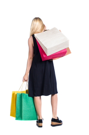 back view of woman with shopping bags . beautiful brunette girl in motion.  backside view of person.  Rear view people collection. Isolated over white background. Long-haired blonde in a black dress holding a paper bag in his hand. Stock Photo