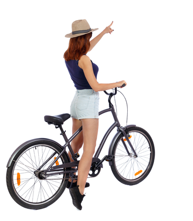 back view of pointing woman with a bicycle. cyclist sits on the bike. Rear view people collection.  backside view of person. Isolated over white background. Girl in a straw hat shows his hand forward with the bike. Stock Photo