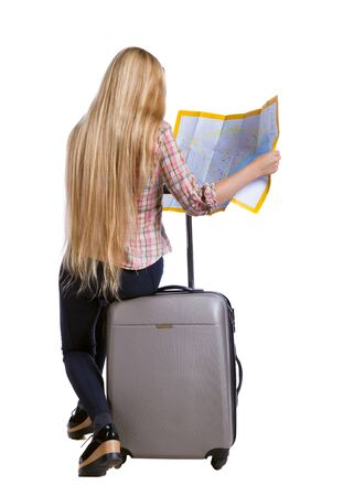 map case: back view of woman traveler sitting on their suitcases and looking for a route map. backside view of person.  Rear view people collection. Isolated over white background. Long-haired girl sitting on a suitcase and looking at the map.
