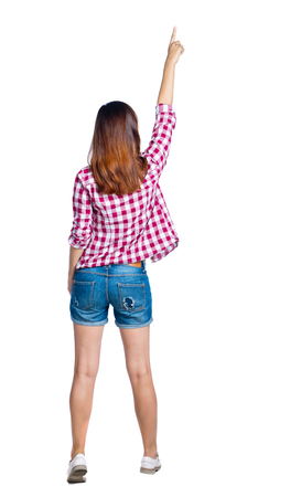 Back view of  pointing woman. beautiful girl. Rear view people collection.  backside view of person.  Isolated over white background. Girl in shorts and a plaid shirt is pointing to the top. photo