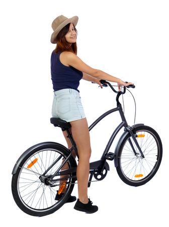 back side view of a woman with a bicycle. cyclist sits on the bike. Rear view people collection.  backside view of person. Isolated over white background. A smiling girl in a straw hat sitting on a bicycle. photo