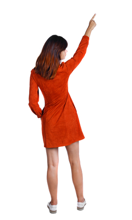 Back view of  pointing woman. beautiful girl. Rear view people collection.  backside view of person.  Isolated over white background. The girl in a red dress shows a finger to the sky. photo