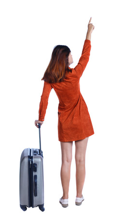 Back view of  pointing woman with suitcase looking up. Standing young girl. Rear view people collection.  backside view of person. Isolated over white background. Girl in red dress standing with gray suitcase and shows up finger. photo