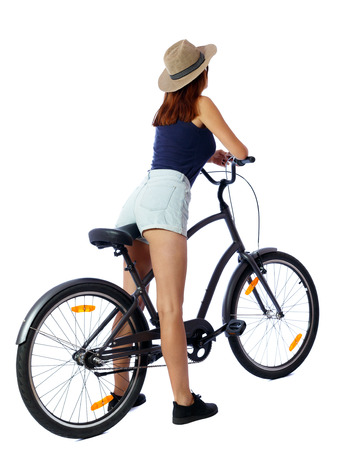 back view of a woman with a bicycle. cyclist sits on the bike. Rear view people collection.  backside view of person. Isolated over white background. Beautiful girl in shorts leaned against the handlebar. photo
