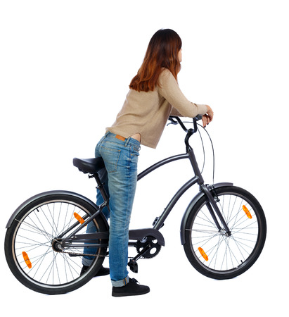 back view of a woman with a bicycle. cyclist sits on the bike. Rear view people collection.  backside view of person. Isolated over white background. The girl in a brown sweater is leaning on the steering wheel. photo