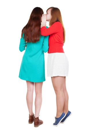 Two young  women friend gossiping.  close up. backside view of person. Isolated over white background. Rear view people collection. standing on tiptoes girl whispers in the ear of his girlfriend. Stock Photo