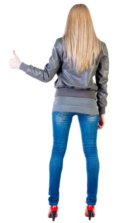 back view of standing young blonde woman showing thumb up. beautiful girl in jeans and red kitten heels gesturing ok sign. Rear view people collection.  backside view of person.  Isolated over white background Stock Photo