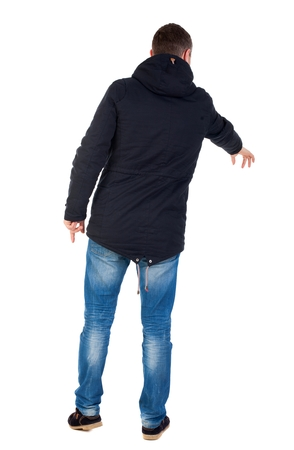 Back view of  pointing young men in parka. Young guy  gesture. Rear view people collection.  backside view of person.  Isolated over white background. Man in warm jacket with his left hand points down.
