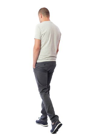 Back view of going  handsome man. walking young guy . Rear view people collection.  backside view of person.  Isolated over white background. A guy in a white T-shirt and trousers leaves, bending his head downward