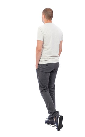Back view of going  handsome man. walking young guy . Rear view people collection.  backside view of person.  Isolated over white background. A guy in a white T-shirt and trousers is pushing his hands in his pockets.