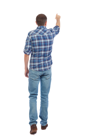 Back view of going  handsome man in jeans pointing. walking young guy . Rear view people collection.  backside view of person.  Isolated over white background. A man in a blue shirt is going to show up. Stock Photo