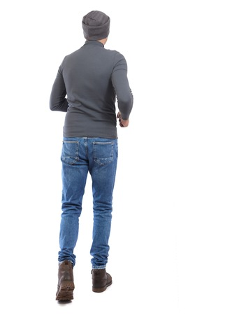 Back view of going  handsome man. walking young guy . Rear view people collection.  backside view of person.  Isolated over white background. A man in a gray sweater and a hat runs away