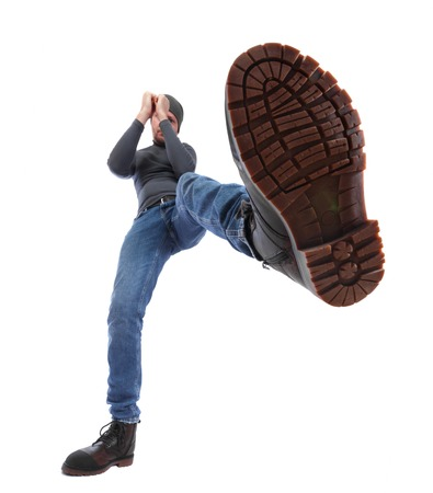 The man is kicking. Foot with a shoe close-up. Corrugated sole of the boot in the frame