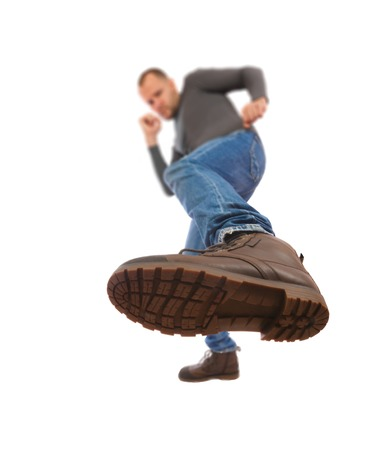 The man is kicking. Foot with a shoe close-up. a man draws an opponent with a boot. Stock Photo