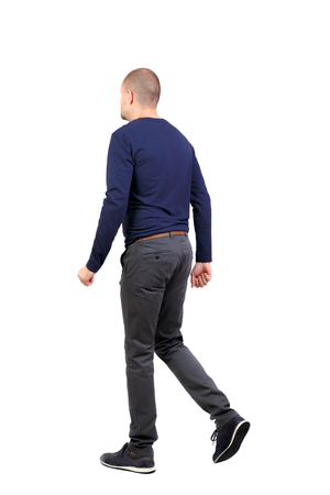 Back view of going  handsome man. walking young guy . Rear view people collection.  backside view of person.  Isolated over white background. A man in trousers and sneakers goes side by side. Stock Photo