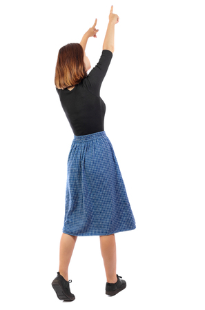Back view of  pointing woman. beautiful girl. Rear view people collection.  backside view of person.  Isolated over white background.  A girl in a blue skirt in hands shows up