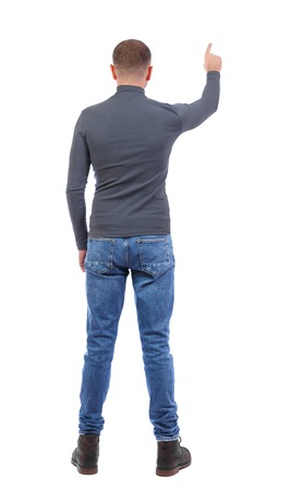 Back view of  pointing young men in  shirt and jeans. Young guy  gesture. Rear view people collection.  backside view of person.  Isolated over white background. a shortly cropped man in a dark jacket shows his hand up.