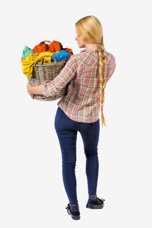 Back view of woman with  basket of dirty laundry. girl is engaged in washing. Rear view people collection.  backside view of person.  Isolated over white background. Girl with braided hair in a braid holding a basket with colorful linens. Stock Photo