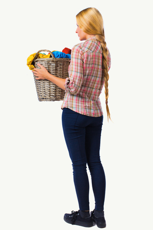 Back view of woman with  basket of dirty laundry. girl is engaged in washing. Rear view people collection.  backside view of person.  Isolated over white background. Girl with very long hair holds up a laundry basket.