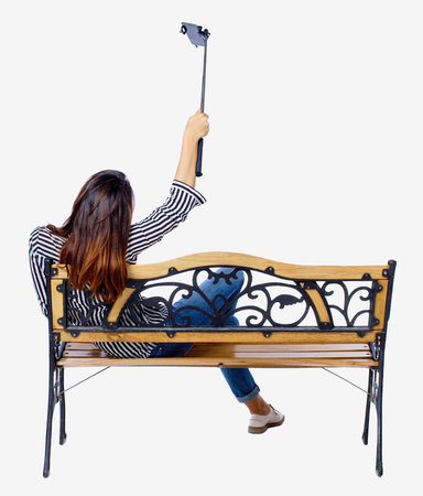 Back view of a woman to make a selfie stick portrait sitting on the bench. girl watching. Rear view people collection. backside view of person. Isolated over white background. Girl on a bench in the park is photographed. Stock Photo