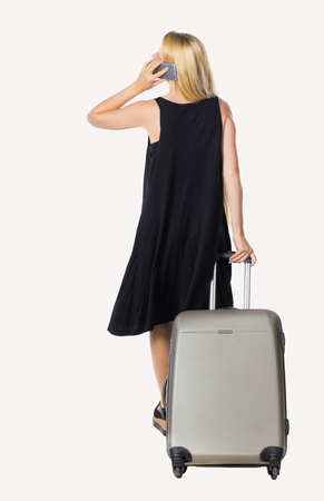 Back view of woman with suitcase talking on the phone. Standing young girl. Rear view people collection.  backside view of person. Isolated over white background. Long-haired blonde in a black dress talking on the phone holding a suitcase.