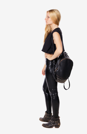 back view of standing young beautiful  woman.  girl  watching. Rear view people collection.  backside view of person.  Blonde in leather pants standing with a backpack resting sideways hand side. Stock Photo