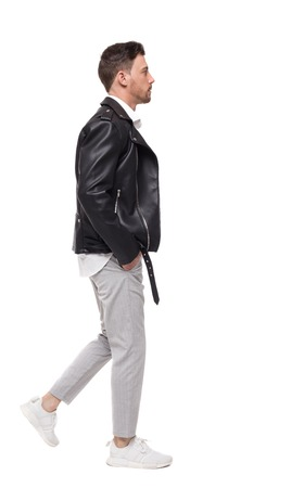 Side view of going  handsome man in a leather jacket and trousers. walking young guy . people collection.  backside view of person.  Isolated over white background. The rocker goes past the frame Stock Photo