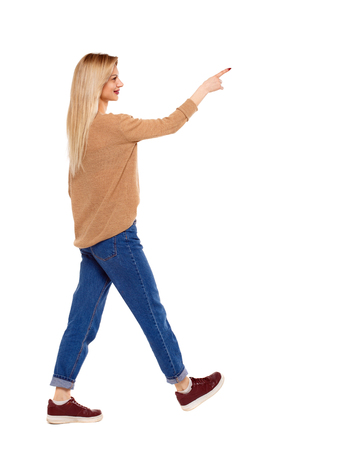 Side view of a girl walking with a pointing hand. going girl showing.  backside view of person.  Rear view people collection. Isolated over white background. Blonde in red sneakers in a hurry