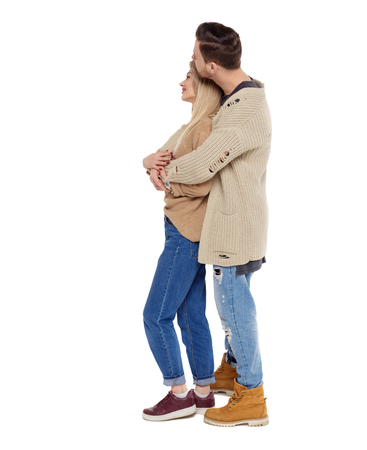 Side view of a stylish couple. beautiful friendly girl and guy together. Rear view people collection.  backside view of person.  Isolated over white background. Husband and wife hugging and looking into the distance