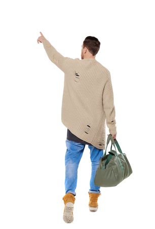 Back view of a walking man with a bag pointing his hand up. backside view of person.  Rear view people collection. Isolated over white background. A hustling traveler in a warm sweater Stock Photo