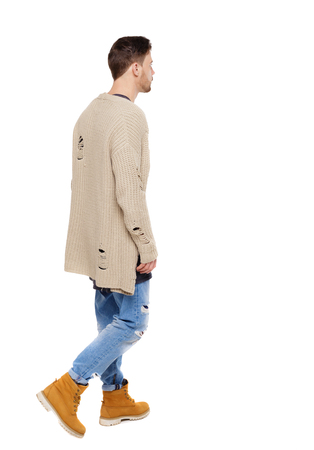 Back view of going  handsome man in a warm sweater. walking young guy . Rear view people collection.  backside view of person.  Isolated over white background. Brunette in a leaky jacket Stock Photo
