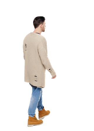 Back view of going  handsome man in a warm sweater. walking young guy . Rear view people collection.  backside view of person.  Isolated over white background. A thoughtful guy in warm clothes slowly wanders