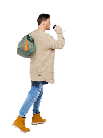 back view of walking  man  with coffee cup and green bag. backside view of person.  Rear view people collection. Isolated over white background. Late student drinks coffee on the go