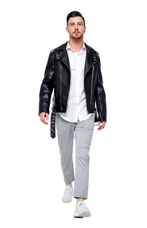 Front view of going  handsome man in a leather jacket and trousers. walking young guy . Front view people collection.  Isolated over white background. Stylish rocker in pants goes smiling