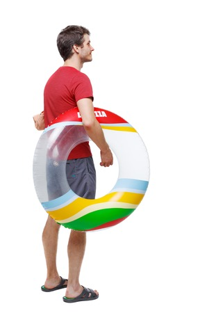 Back view of a man in shorts with an inflatable circle. The guy on the beach. Rear view people collection.  backside view of person.  Isolated over white background. the guy in the red T-shirt came to the pool