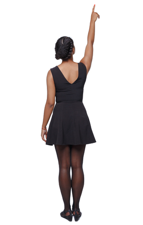back view of a black African-American woman in a brown dress pointing upwards. Rear view people collection.  backside view of person.  Isolated over white background. The girl is giving a presentation