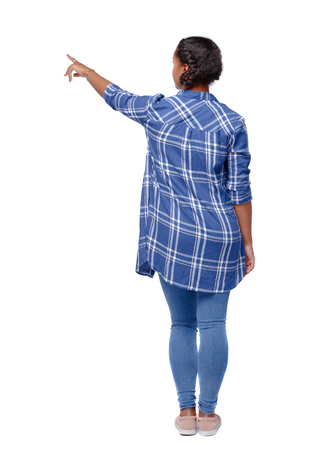 back view of a black African-American woman in a shirt pointing upwards. Rear view people collection.  backside view of person.  Isolated over white background. A girl in a shirt points with her hand to the side