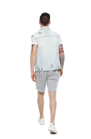 Back view of going  handsome man in a shorts. walking young guy . Rear view people collection.  backside view of person.  Isolated over white background. The guy with the tattoo is slowly retreating into the distance