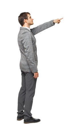 Side view of pointing business man. gesticulating young guy in suit. Rear view people collection.  backside view of person.  Isolated over white background. office worker in a shirt and trousers powerfully indicates something Side. putting his hand on the waist, the other hand businessman showing up