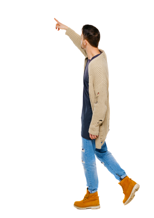 Side view of a man walking with a pointing hand. going  guy showing.  backside view of person.  Rear view people collection. Isolated over white background. The guy in the shoes shows on the sights Imagens